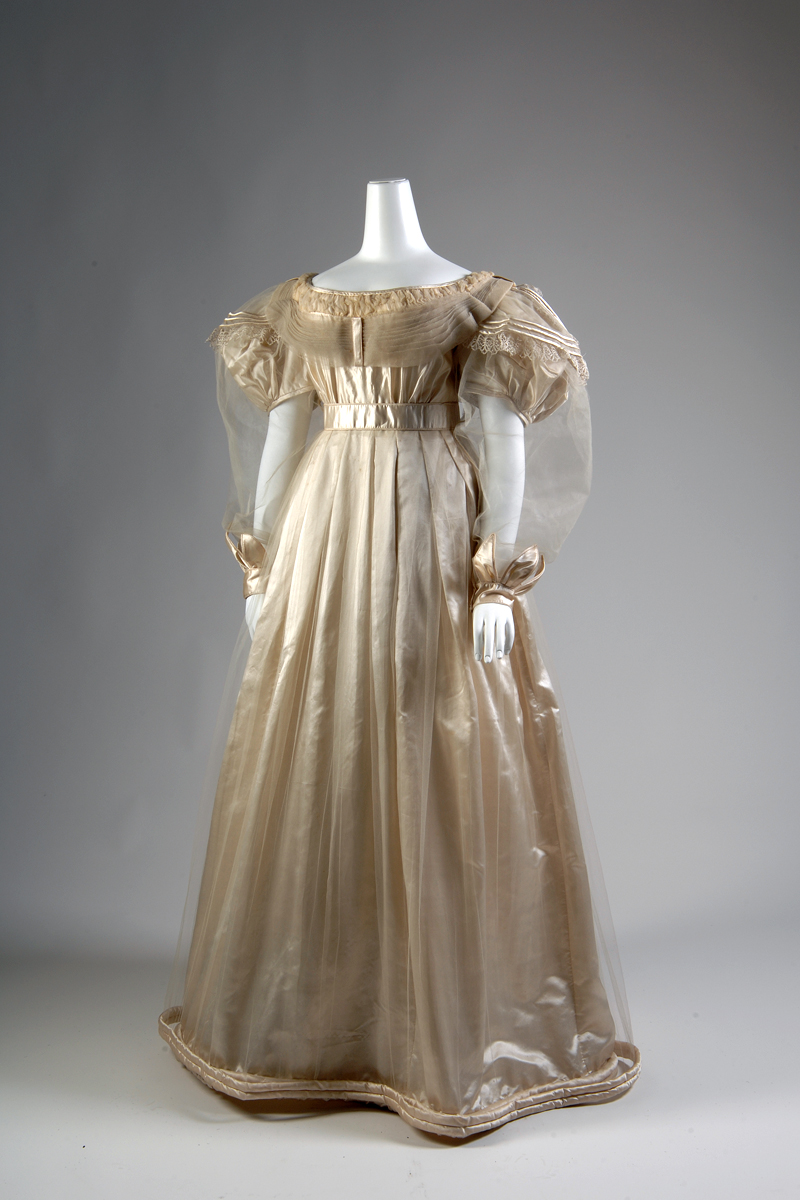 """Cream silk satin ballgown with attached tulle overdress; décolleté gown with chiffon neck ruffle,  empire waist, short puffed sleeves, full length bell skirt with thick rouleau hem bands; tulle overdress with tucked neckline, long sleeves with cuff band of satin appliqué """"petals,"""" long bell skirt with single satin rouleau hem band 