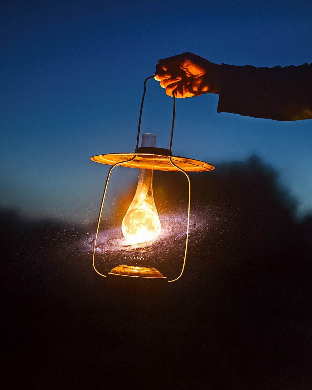 man holding the old lamp with a candle outdoors. hand holds a la